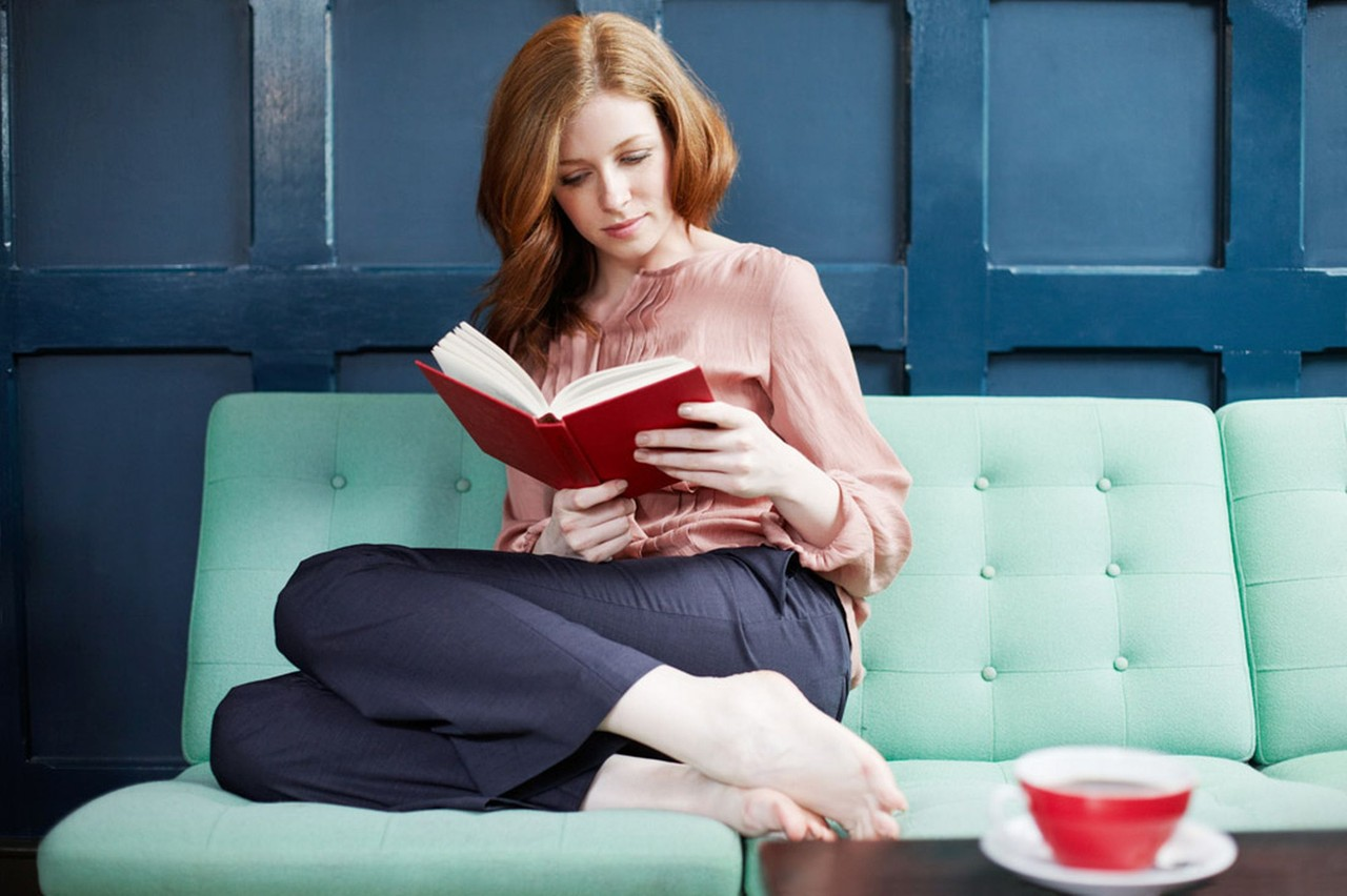 Woman-reading-a-book-on-sofa.jpg